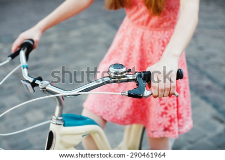 Close up hands of a young girl in pink dress, pressed handbrake on vintage bicycle - stock photo