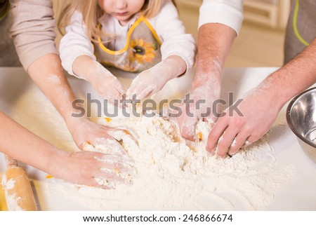 Close-up hands of family are baking cakes in home kitchen. - stock photo
