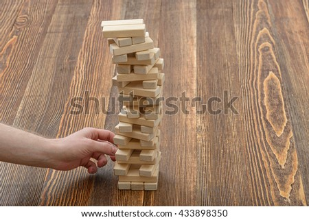 Close-up hands of man pulls out wooden bricks. Removing blocks from a tower. Keeping balance. Full concentration. Entertainment activity. Game of physical and mental skill. Close-up photo. - stock photo