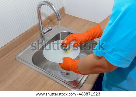 Close up hands of man washing dishes in kitchen
