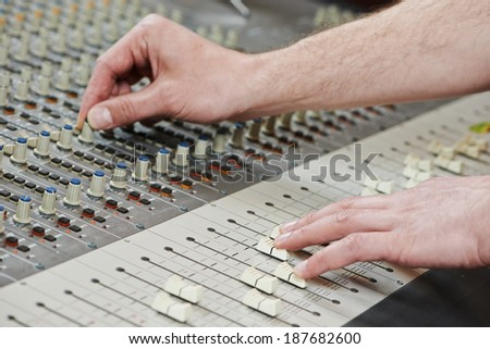 close-up hands of sound engineer work with faders on mixer - stock photo