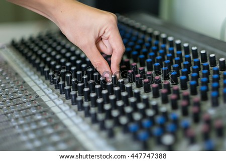 Close up hands of sound engineer working at mixing panel in recording studio.