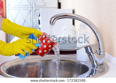 Close up hands of woman washing dishes in kitchen - stock photo
