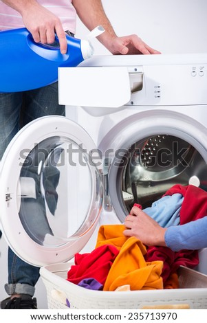 Close-up hands of young couple are doing laundry at home. - stock photo
