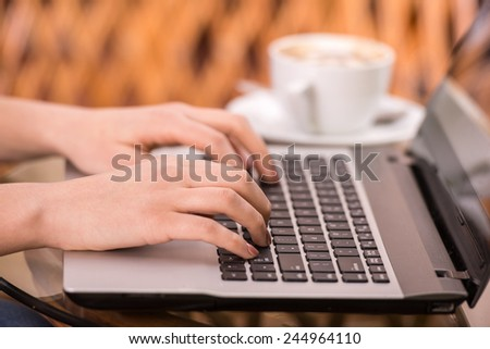 Close-up hands of young woman is using laptop. - stock photo