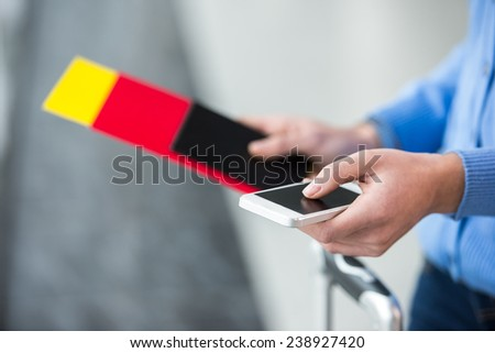 Close-up hands of young woman with passport and smartphone. - stock photo