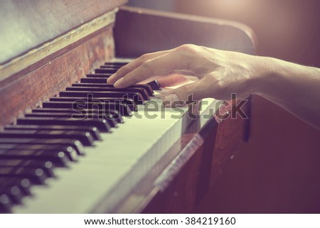 close up hands on the key of the piano,retro tone - stock photo