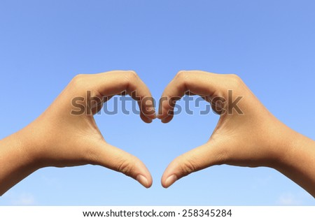 Close up hands with heart sign background with blue sky - stock photo
