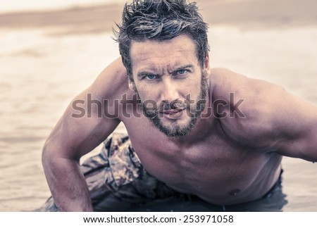 Close up Handsome Athletic Army with No Shirt Crawling at Sea Water While Looking at the Camera. - stock photo