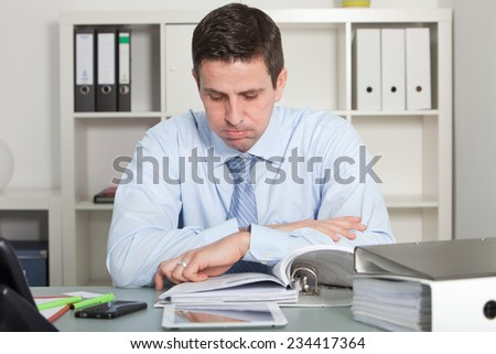 Close up handsome businessman reviewing report papers seriously at his worktable at the office. - stock photo