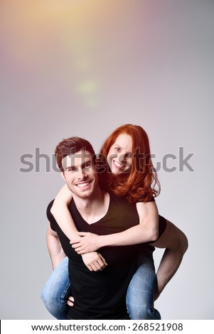 Close up Handsome Man Carrying his Pretty Girl on his Back While Smiling at the Camera. Captured in Studio with Gray Background. - stock photo