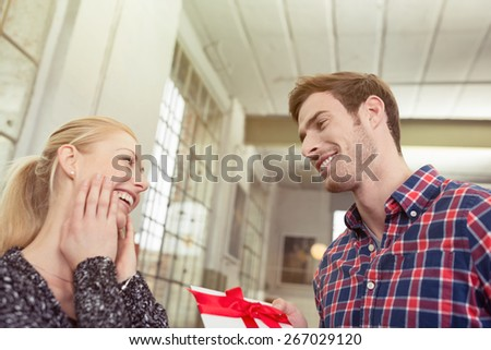Close up Handsome Young Boyfriend Offering Presents to his Pretty Blond Girlfriend with Happy Facial Expression. - stock photo
