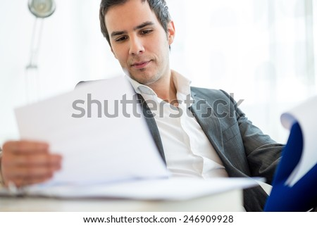 Close up Handsome Young Businessman Reviewing Business Documents at his Table Inside the Office. - stock photo
