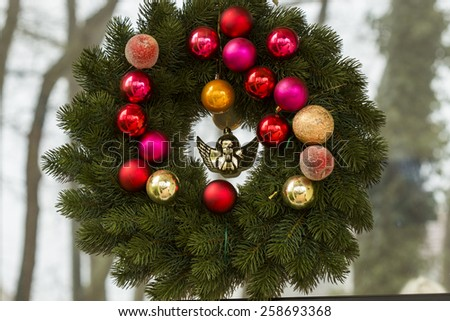 Close up Hanging Christmas Wreath with Balls and Angel Decors on Glass Window - stock photo