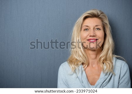 Close up Happy Adult Blond Woman Leaning on Gray Wall Background while Smiling at the Camera. - stock photo