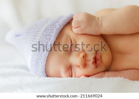 Close up happy baby girl new born sleeping in hat - stock photo