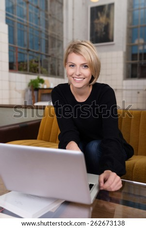 Close up Happy Blond Woman Sitting on the Living Room Sofa, with Laptop Computer on the Table, Looking at the Camera. - stock photo
