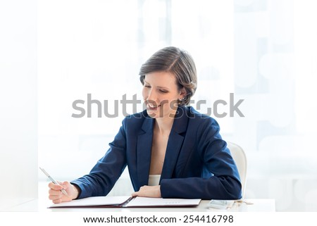 Close up Happy Businesswoman Writing financial report at her Table Inside the Office. - stock photo