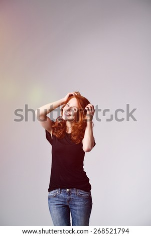 Close up Happy Cute Woman Wearing Casual Black Shirt and Jeans While Holding her Red Hair and Looking at the Camera. Captured in Studio with Gray Background. - stock photo