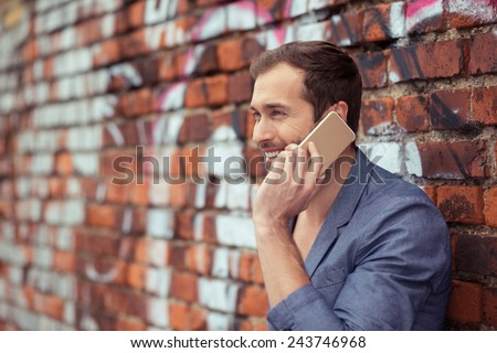 Close up Happy Handsome Young Man Calling Someone Through Mobile Phone While Leaning on Old Brick Wall - stock photo