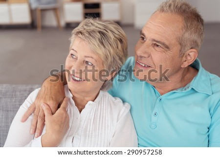 Close up Happy Sweet Middle Aged Couple Looking Into Distance Together While Sitting on the Couch at the Living Room. - stock photo