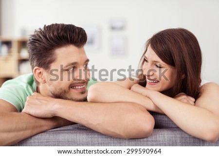 Close up Happy Sweet Young Couple Admiring Each Other with Toothy Smiles While Relaxing on the Couch at the Living Room. - stock photo
