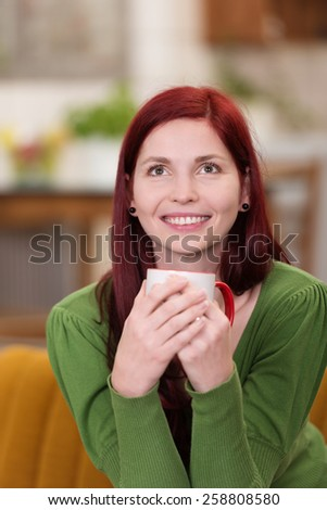 Close up Happy White Woman Wearing Green Long Sleeve Shirt, Sitting on Couch While Looking Up with a Cup of Coffee. - stock photo
