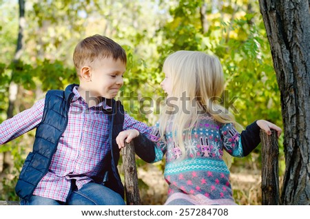 Close up Happy Young Boy and Girl in an Autumn Style Clothing Sitting on the Wooden Garden Fence While Laughing Each Other - stock photo