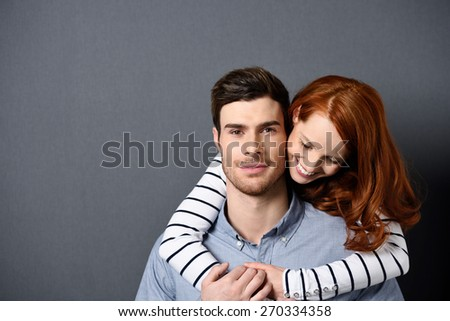 Close up Happy Young Woman Embracing her Handsome Man Looking at the Camera from the Back.Isolated on Gray with Texts Space. - stock photo