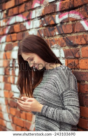 Close up Happy Young Woman in Gray Long Sleeve Shirt Messaging Someone Using Smart Phone While Leaning on Old Brick Wall. - stock photo