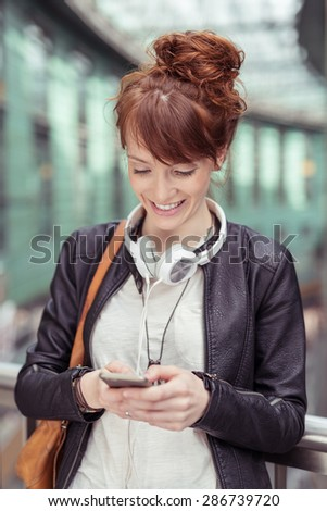 Close up Happy Young Woman in Leather Jacket with Headphone Around her Neck and Shoulder Bag, Busy with her Mobile Phone While Leaning Against the Railings. - stock photo