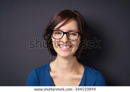 Close up Happy Young Woman, Wearing Eyeglasses, Showing Toothy Smile at the Camera Against Gray Wall Background. - stock photo