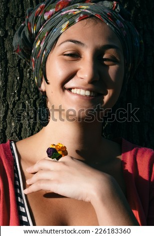 Close up Happy Young Woman with Head Cover and Floral Ring Leaning on Tree.