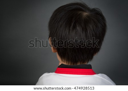 Close up Head of Asian child training from balk side in TAEKHONDO uniform on gray background