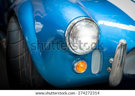 Close Up Headlight Detail of Blue Classic car - stock photo