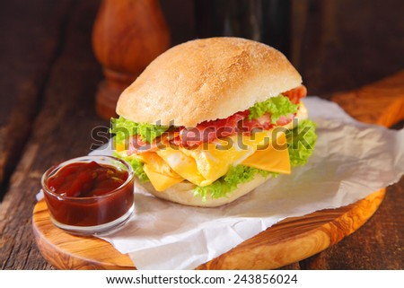 Close up Healthy Egg Burger with Ketchup on Saucer Placed on Burger Paper Above Wooden Serving Board. - stock photo