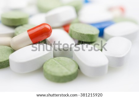 Close-up. Heap of medicine multi colored pills on white surface.
