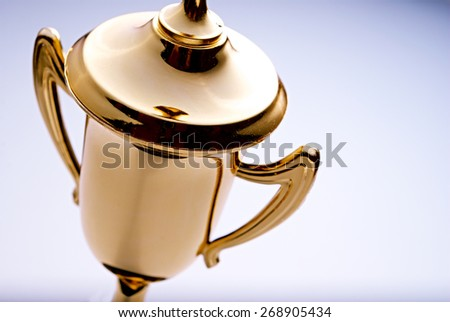 Close up high angle view of a shiny gold trophy award to be awarded to the winner or champion in a competition, with copyspace to the right - stock photo