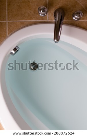Close up high angle view of a sunken oval bathtub full of clean fresh water ready for a lovely relaxing bath - stock photo