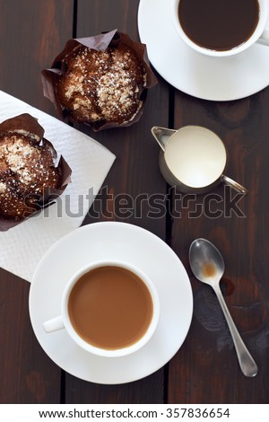 Close up high angle view of two cups of coffee with two muffins - stock photo
