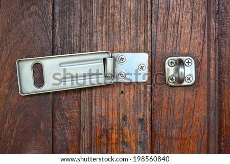 Close up hinge lock on wooden door background. - stock photo