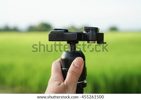 Close up hold camera tripod by human hand with green field background - stock photo