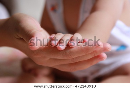 Close Up holding baby hand