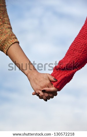 Close-up Holding Hands against blue ski background - stock photo