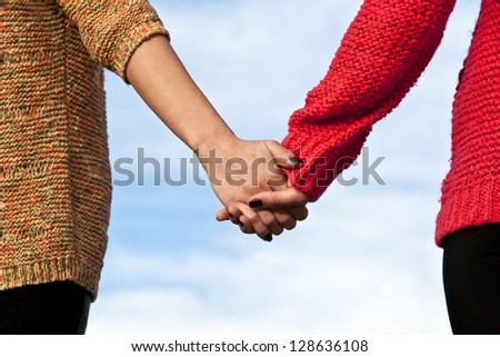 Close-up holding hands on blue ski background - stock photo