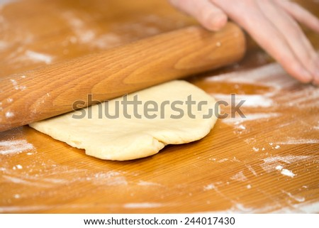 Close up homemade cooking, female hands roll out pastry with wooden dough roller on wooden table covered in flour