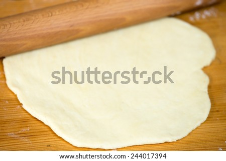 Close up homemade cooking, flat dough with rolling-pin on wooden table - stock photo