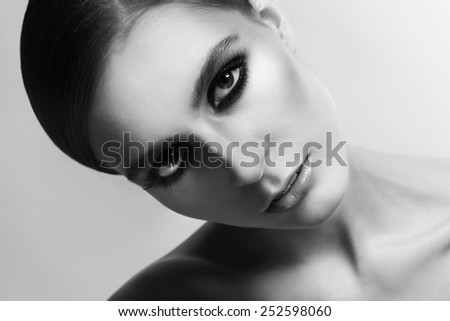 Close-up horizontal black and white portrait of young beautiful woman with smokey eyes - stock photo