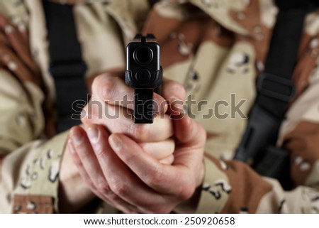 Close up horizontal image of pistol, pointing forward, with armed male soldier in background. Focus on front part of weapon with soldier blurred out.