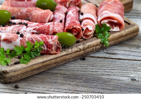 Close up horizontal image of various meats on serving board with ham, pork, beef, parsley, and olives on rustic wood. Focus on side part of serving board and first row of meat.   - stock photo